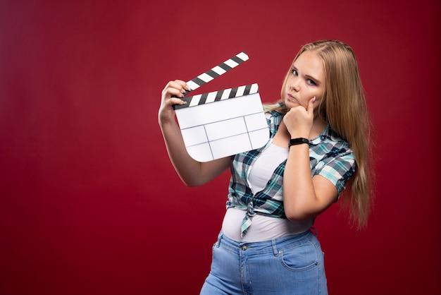 Молодая белокурая модель, держащая пустую доску с хлопушкой для съемок фильма.