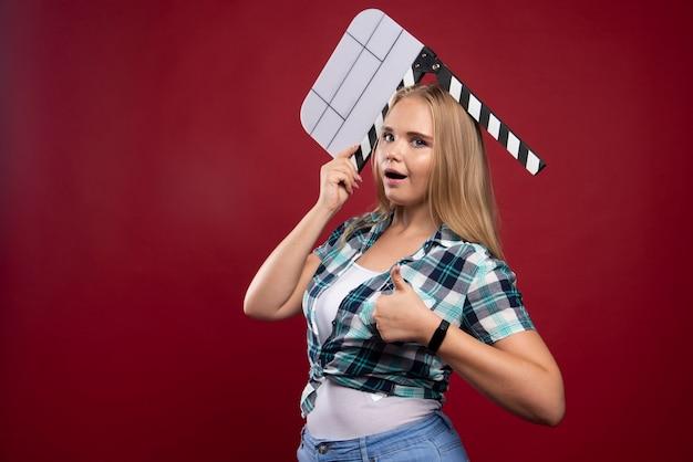 Giovane modella bionda che tiene un ciak film in bianco e si diverte.