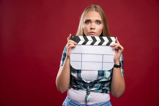 Giovane modella bionda che tiene in mano un ciak per le riprese di un film vuoto e sembra stressata e inesperta.