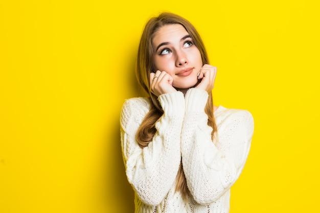 黄色の若いブロンドモデルは恋に落ちて彼女の手でハート記号を示しています