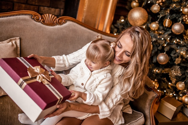 Young blonde mother and her daughters in white knitted clothes opening a magical christmas gift by a christmas tree in cozy living room in winter