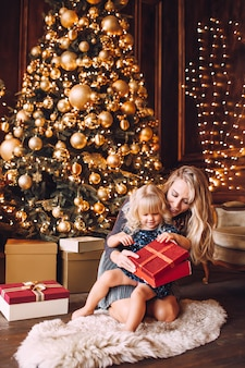 Young blonde mother and her little daughter in shiny clothes opening a christmas gift near a christmas tree in cozy living room in winter