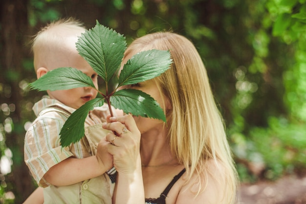 A young blonde mother holds her little son in her arms and plays with him hiding behind a leaf