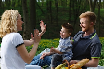 Young blonde mother plays with her son during a picnic in the park