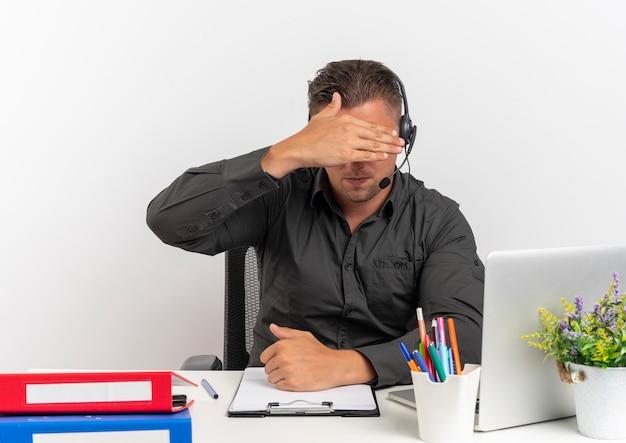 ヘッドフォンで若い金髪のサラリーマンの男は、コピースペースで白い背景で隔離の手で顔を隠すラップトップを使用してオフィスツールで机に座っています