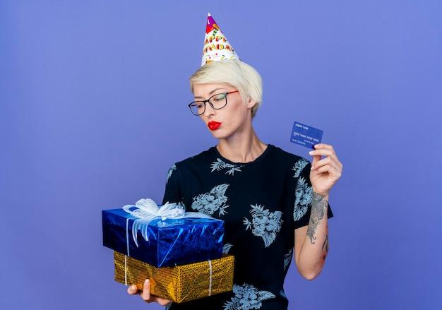 Giovane ragazza bionda festa con gli occhiali e cappello di compleanno che tiene scatole regalo e carta di credito guardando le caselle isolate su sfondo viola con spazio di copia