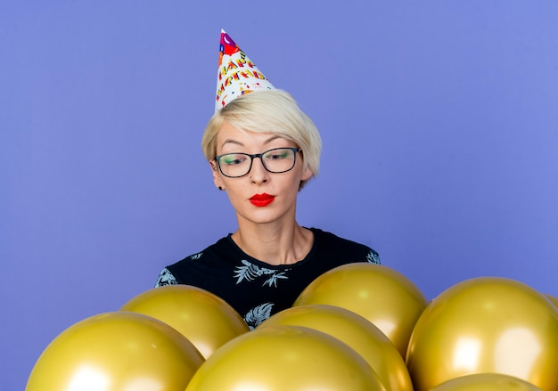 Young blonde party girl wearing glasses and birthday cap standing behind balloons looking at them isolated on purple background