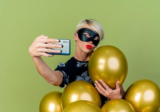 Bionda e giovane ragazza di partito che indossa la maschera di travestimento in piedi dietro i palloncini afferrando uno di loro facendo gesto di bacio tenendo selfie isolato su sfondo verde oliva