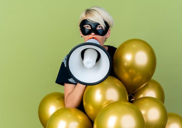 Giovane ragazza bionda di partito che indossa la maschera di travestimento in piedi dietro i palloncini che guarda l'obbiettivo parlando da altoparlante isolato su sfondo verde oliva con lo spazio della copia