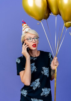 Young blonde party woman wearing glasses and birthday cap holding balloons looking at side talking on phone isolated on purple wall