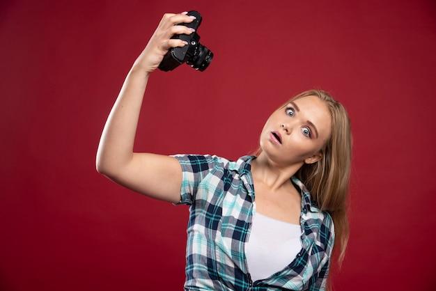 전문 카메라를 들고 젊은 금발 사진과 이상한 위치에 그녀의 셀카를 걸립니다.