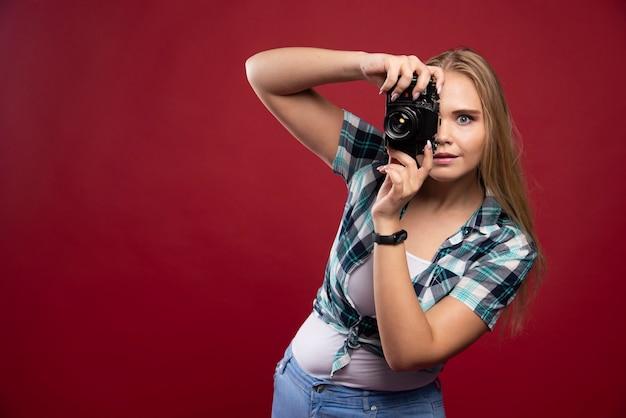 Giovane fotografia bionda in possesso di una macchina fotografica professionale e servizio fotografico in modo professionale.
