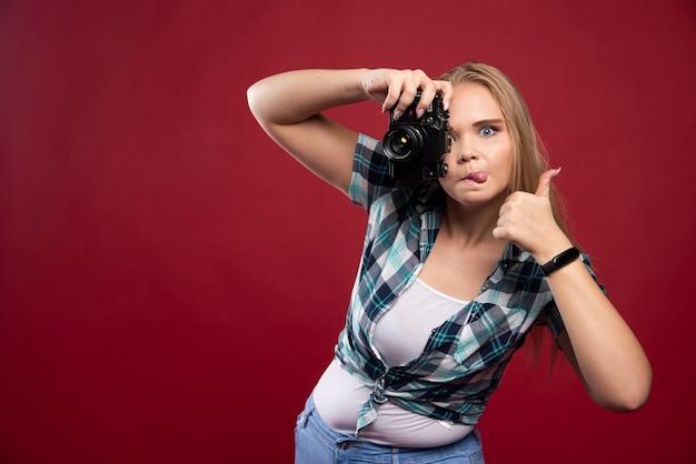 Giovane bionda fotografa in possesso di una macchina fotografica professionale e si fa il selfie in strane posizioni.