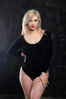 黒のボディースーツで明るい化粧品で若い金髪肉付きの良い女性がポーズをとってください。
