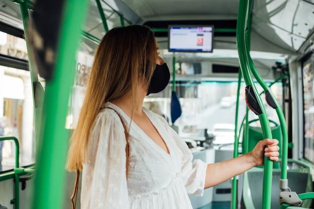 도시 버스 여행을 만드는 얼굴 마스크와 젊은 금발 임신 한 여자. 버스 정류장에서 내리기를 기다리고 있습니다.