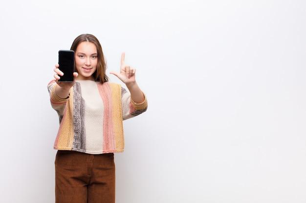 Молодая белокурая милая девушка держа smartphone