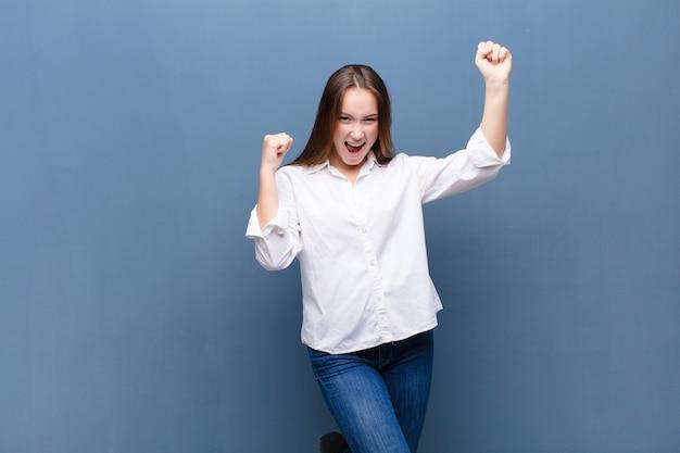 意気揚々と叫んでいる若いブロンドのかわいい女の子は、コンクリートの壁を祝って興奮し、幸せで驚いた勝者のように見えます