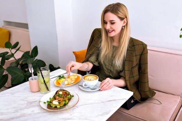 Giovane donna bionda piuttosto sorridente che gode di un gustoso brunch sano con toast di avocado al salmone, cappuccino, limonata e dessert, vestito elegante, interni di fantasia leggera.