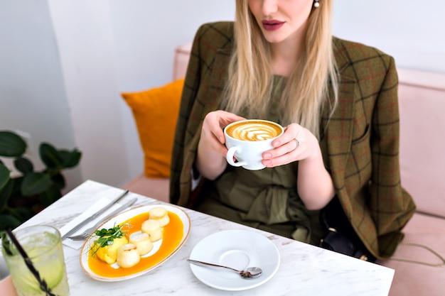 Giovane donna graziosa bionda che gode di un gustoso brunch sano con toast di avocado al salmone, cappuccino, limonata e dessert, vestito elegante, interni di fantasia leggera, che tiene una tazza di caffè.