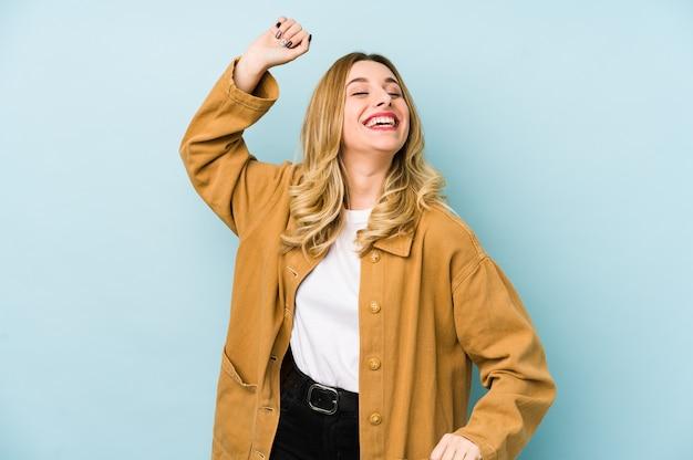 特別な日を祝って孤立した若い金髪のきれいな女性は、エネルギーでジャンプして腕を上げます。