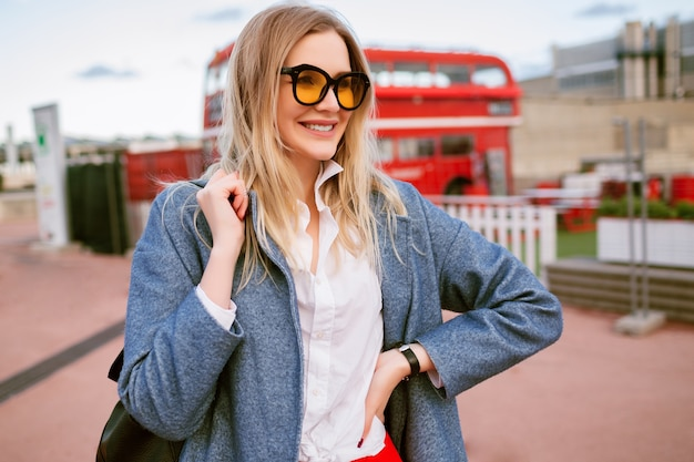 Young blonde pretty woman walking at london city center, wearing stylish smart casual student outfit, blue coat and colored glasses , autumn spring mid season time, traveling mood.