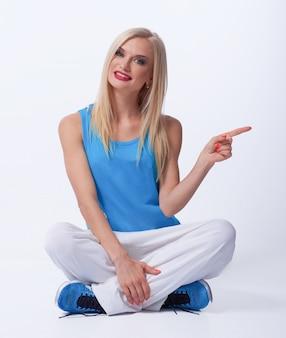 床の選択の推奨事項にリラックスして座っている彼女の指で側を指している若いブロンドの赤い唇のスポーツウーマン