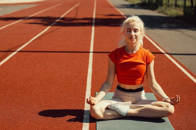 Молодая блондинка расслабляется на спортивном коврике