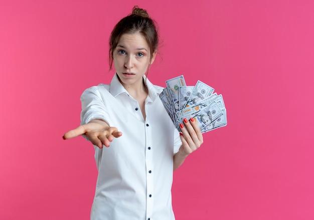 Молодая блондинка русская девушка протягивает руку, держа деньги на розовом с копией пространства