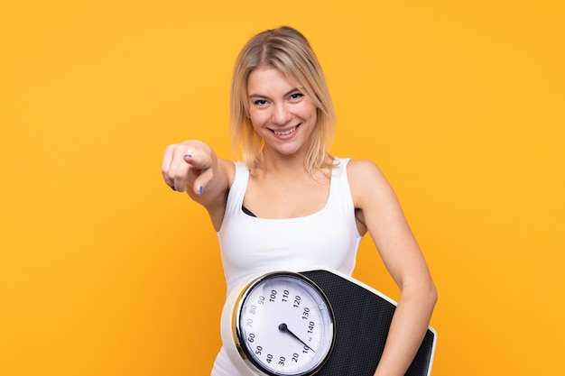 Young blonde russian woman holding a weighing machine and pointing to the front