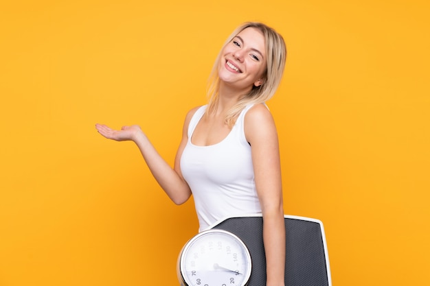 Young blonde russian woman over isolated yellow wall with weighing machine