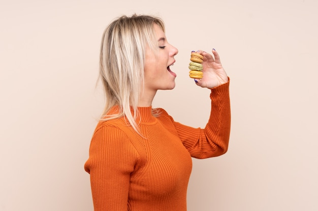 Молодая белокурая русская женщина над изолированной стеной держит красочные французские macarons и ест его