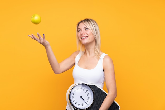 Young blonde russian woman with weighing machine and with an apple