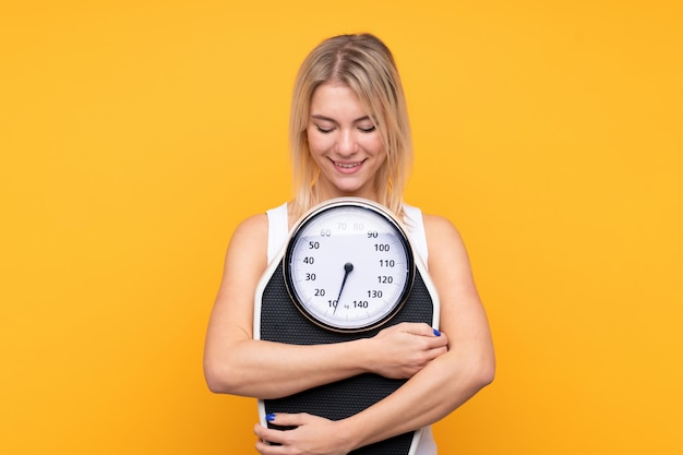 Young blonde russian woman with weighing machine