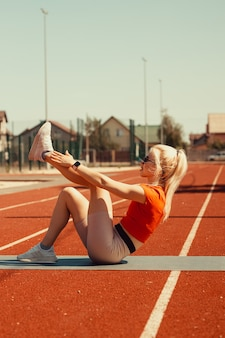 Молодая блондинка качает мышцы живота на спортивном коврике на улице