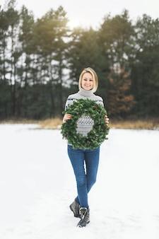 Молодая блондинка с короткими волосами в сером вязаном свитере держит рождественский венок