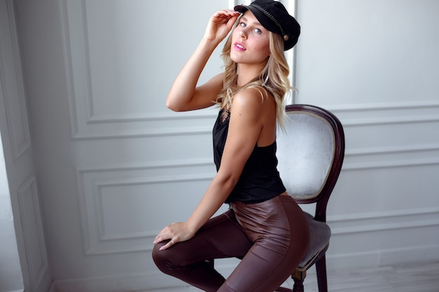 Young blonde in a silk blouse and leather pants poses against a white wall. catalog beauty salon party. idea and concept of health, youth and proper self-care