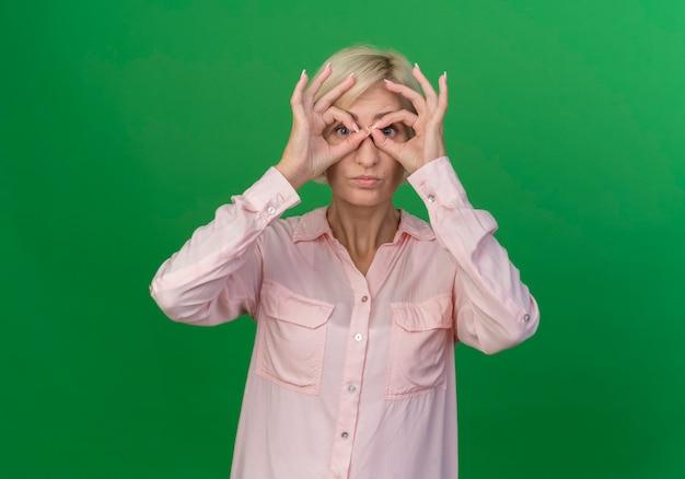 Молодая блондинка славянская женщина делает жест взгляда в камеру, используя руки как бинокль, изолированные на зеленом фоне