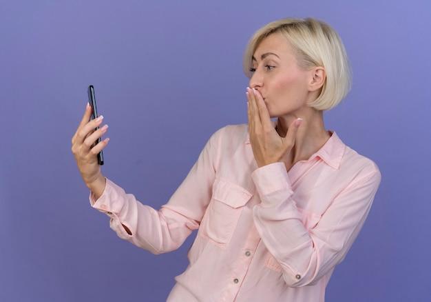 紫色の背景で隔離の携帯電話で見てキスジェスチャーを保持している若い金髪のスラブ女性