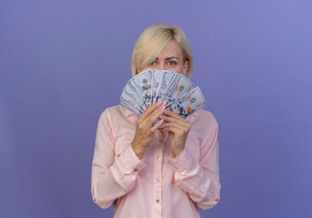 Giovane donna slava bionda che tiene i soldi e che guarda l'obbiettivo da dietro il denaro isolato su sfondo viola con spazio di copia