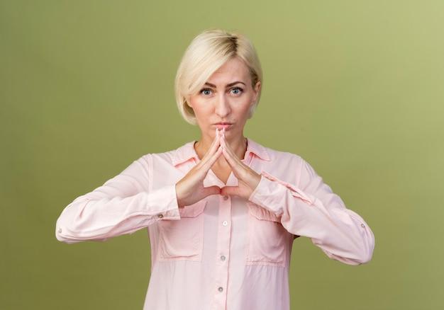 Молодая блондинка славянская женщина показывает знак треугольника