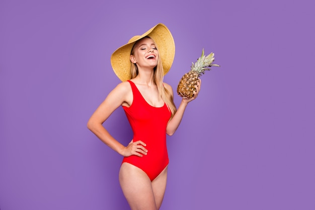 Young blonde smiling girl wearing red swimsuit and sunhat holding pine apple