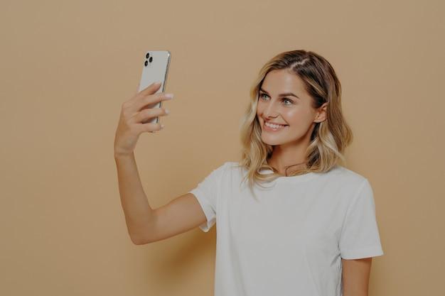 Молодая блондинка улыбается женщина с помощью смартфона во время видеозвонка с семьей или другом, одетая в белую футболку, глядя на мобильную камеру и улыбаясь. современные технологии и коммуникационная концепция