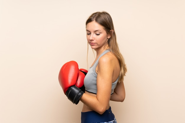 Young blonde sport girl over isolated wall with boxing gloves
