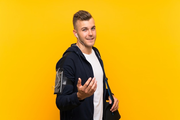 Young blonde sport man over isolated yellow background inviting to come with hand. happy that you came