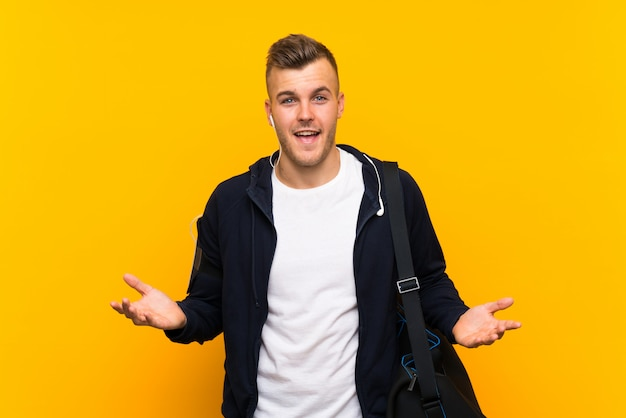 Young blonde sport man over isolated yellow background with shocked facial expression