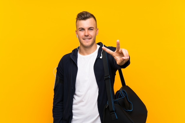 Young blonde sport man over isolated yellow wall smiling and showing victory sign