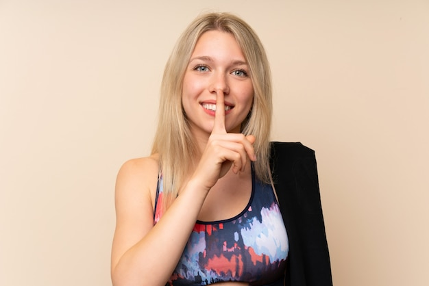 Young blonde sport woman over isolated wall doing silence gesture