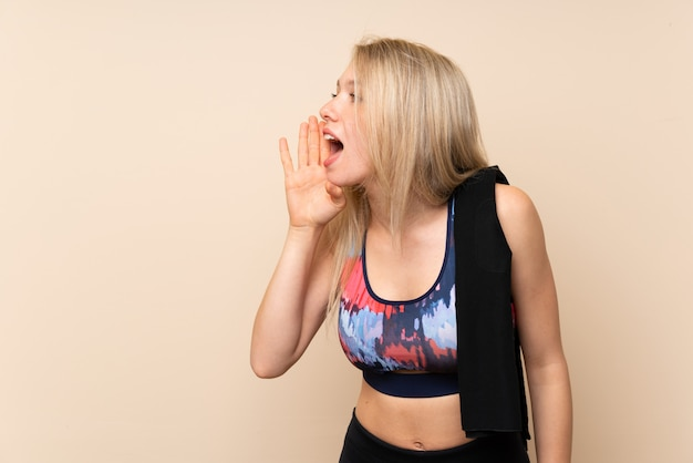 Young blonde sport woman over isolated wall shouting with mouth wide open