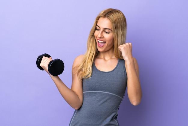 Молодая белокурая женщина спорта делая поднятие тяжестей над изолированным пурпуром празднуя победу