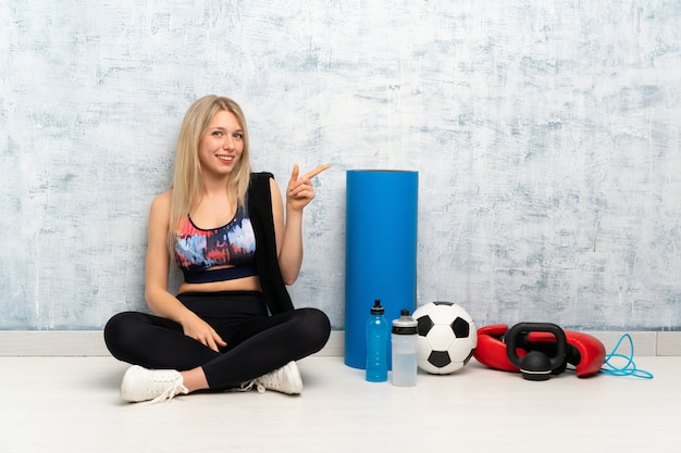 Young blonde sport woman sitting on the floor pointing finger to the side